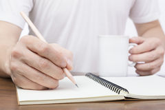 Man writing on notebook and holding a cup of hot drink Royalty Free Stock Images