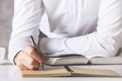 Man writing in notepad. Close up of male hand writing in notepad Stock Image