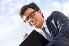 Man writing in notepad closeup. Portrait of attractive smiling businessman in glasses taking notes on notepad. Blurry sky background Royalty Free Stock Photos