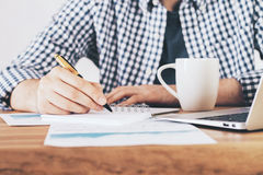 Man writing in notepad front. Frontview of male hand writing in spiral notepad on desk with coffee mug, laptop and business report Royalty Free Stock Image
