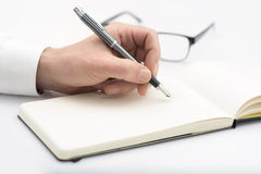 Man writing. On a notepad and glasses behind royalty free stock image