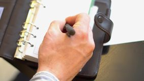 Man writing in Notepad. A man makes an entry in his notebook top view stock footage
