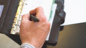 Man writing in Notepad. A man makes an entry in his notebook top view stock video footage