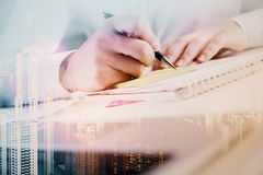 Man writing in notepad multiexposure. Close up of male hands writing in notepad on abstract city background. Double exposure Royalty Free Stock Images