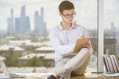 Man writing in notepad. Portrait of handsome young businessman writing in notepad while sitting on windowsill with coffee cup and books. Blurry city view in the Stock Photography