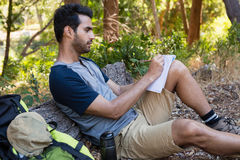 Man writing on notepad while resting on tree trunk Stock Images