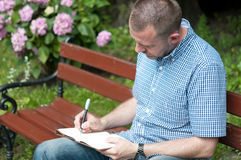 Man Writing in Notepad Royalty Free Stock Image