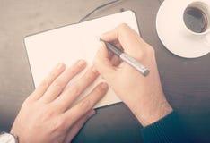 Man writing notes at the cafe Stock Photos
