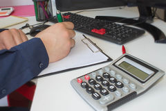 Man writing notes from computer on wooden table. Man hand with pen, calculator and computer on table Stock Images