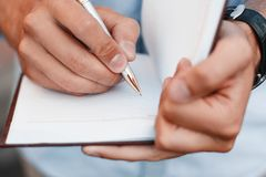 Man writing notes in a notebook. Hand holding pen. Blank Stock Image