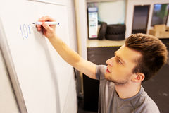 Man writing numbers to whiteboard in gym. Sport, fitness and people concept - man writing numbers to whiteboard in gym Royalty Free Stock Images