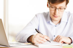 Man writing in office. Frontview of focused businessman writing in notepad at desk with laptop Royalty Free Stock Photo