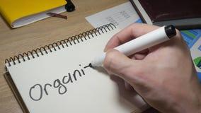 Man writing Organization at note.