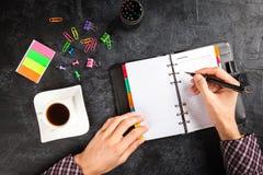 Man writing in organizer Stock Photography