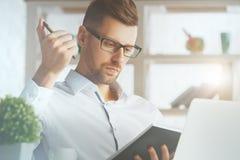 Man writing in organizer Stock Image