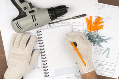 Man writing in pad with drill Royalty Free Stock Images