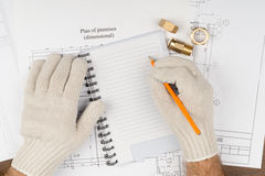 Man writing in pad with pipe fittings Stock Photos
