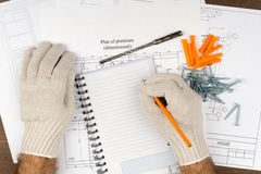 Man writing in pad with screws Stock Images