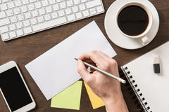 Man writing on paper on home office table stock images