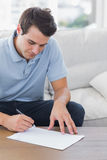 Man writing on a paper while he is sat on a couch Royalty Free Stock Photos