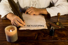Man writing on a parchment Invitation Stock Images