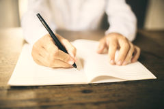 Man writing with pen in blank notebook on wooden table Stock Images