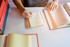 Man writing pen in book on white table Stock Photo