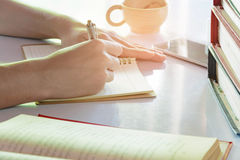 Man writing pen in book on white table Royalty Free Stock Images