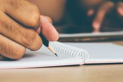 Man is writing with a pencil on a piece of paper Stock Image