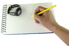 Man writing with a pencil on a spiral bound book and wrist watch. Man writing with a yellow pencil on a blank white spiral bound book holding the pen in his hand Stock Images