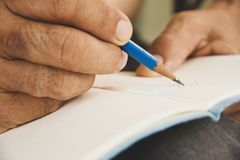 Man writing on sketchbook Stock Images