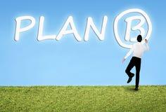 Man writing on sky Plan B word Stock Images