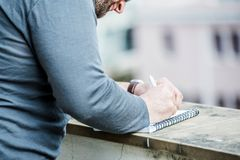 Man writing something on a notebook - close up side view Royalty Free Stock Photo