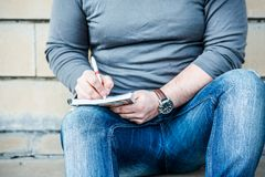 Man writing something on a notebook Stock Photos
