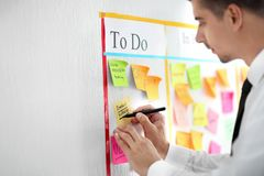 Man writing on sticky note attached to scrum task board in office royalty free stock photography
