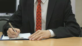 Man writing the text using a ball point pen