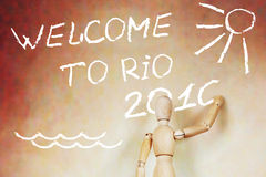 Man writing text Welcome to Rio 2016. Abstract conceptual image with a wooden puppet Stock Photography