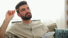 Man writing to notebook and thinking at home