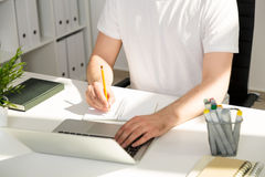 Man writing and using laptop. Man sitting at office desk, using laptop and writing in notepad Stock Images