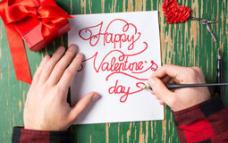 Man writing a Valentines day card and preparing present Stock Photography