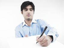Man writing on a white board. Asian male of indian origin writing with a felt pen Royalty Free Stock Photos