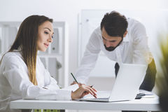 Man writing and woman working at laptop Royalty Free Stock Photos