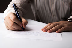 Man is  writting on a sheet of paper Royalty Free Stock Photography