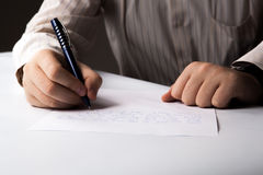 Man is  writting on a sheet of paper Stock Photo
