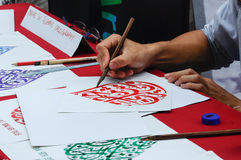 A man wrote an Arab calligraphy. MALACCA, MALAYSIA - NOVEMBER 01, 2015: A man wrote an Arab calligraphy words on piece of paper Royalty Free Stock Image