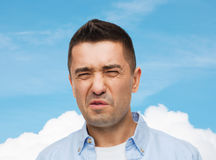 Man wrying of unpleasant smell. Emotions, facial expression and people concept - man wrying of unpleasant smell over blue sky and cloud background Stock Photos