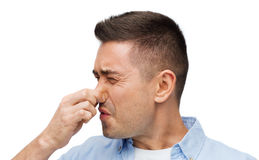 Man wrying of unpleasant smell. Emotions, gesture and people concept - man wrying of unpleasant smell and closing his nose stock photos