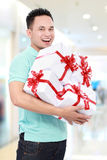 Man wth many gift boxes. Young man carrying many gift boxes shopping in the mall Royalty Free Stock Image