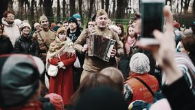 Man in ww2 soviet soldier uniform playing harmonica and sing with crowd stock video footage
