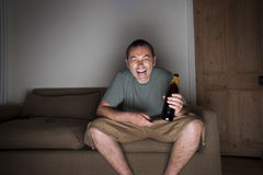 Man wwatching tv drinking beer and laughing Royalty Free Stock Photo